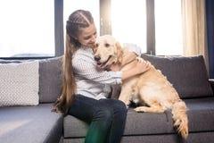 Muchacha que abraza el perro del golden retriever en el sofá en casa Foto de archivo