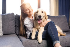 Muchacha que abraza el perro del golden retriever en el sofá en casa Foto de archivo libre de regalías