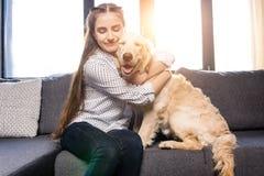Muchacha que abraza el perro del golden retriever en el sofá en casa Fotografía de archivo libre de regalías