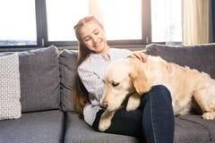 Muchacha que abraza el perro del golden retriever en el sofá en casa Fotos de archivo libres de regalías