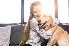 Muchacha que abraza el perro del golden retriever en el sofá en casa Imagen de archivo libre de regalías