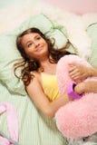 Muchacha que abraza la almohadilla Imagen de archivo libre de regalías