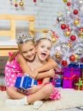 Muchacha que abraza a otra muchacha que se sienta en una manta con un regalo en el árbol de navidad Imagenes de archivo
