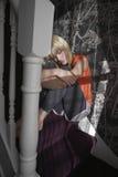 Muchacha que abraza rodillas en pasos en casa Foto de archivo