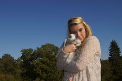 Muchacha que abraza su conejo Imagen de archivo libre de regalías