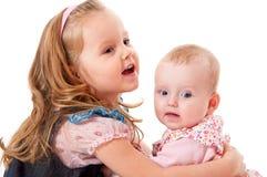 Muchacha que abraza a su hermana más joven Imágenes de archivo libres de regalías