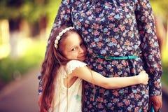 Muchacha que abraza a su madre Imagen de archivo libre de regalías