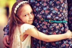 Muchacha que abraza a su madre Imágenes de archivo libres de regalías