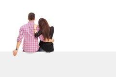 Muchacha que abraza a su novio asentado en un panel Imagenes de archivo
