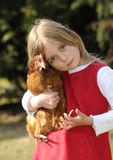 Muchacha que abraza un pollo Foto de archivo