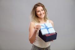 Muchacha que abre un presente aislado Imagenes de archivo