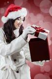 Muchacha que abre un regalo de la Navidad Imagenes de archivo