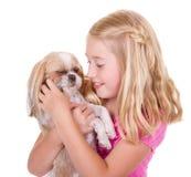 Muchacha que acaricia su perro del tzu del shih Fotos de archivo