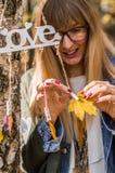 muchacha que acorta la hoja amarilla Fotografía de archivo
