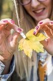 muchacha que acorta la hoja amarilla Fotografía de archivo libre de regalías