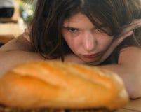 Muchacha que adelgaza adolescente en mirada de la dieta en la expresión del anhelo del wigh del pan del pan Imagen de archivo libre de regalías