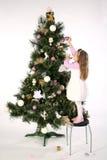 Muchacha que adorna el árbol Imagen de archivo libre de regalías