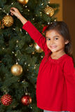 Muchacha que adorna el árbol de navidad Imágenes de archivo libres de regalías
