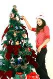 Muchacha que adorna el árbol de navidad Imagenes de archivo