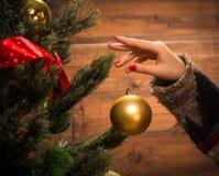 Muchacha que adorna el árbol del Año Nuevo con las bolas de la Navidad Foto de archivo libre de regalías