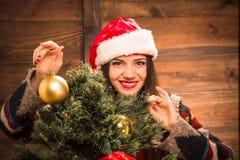Muchacha que adorna el árbol del Año Nuevo con las bolas de la Navidad Fotos de archivo
