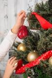 Muchacha que adorna el árbol del Año Nuevo en casa Fotos de archivo libres de regalías