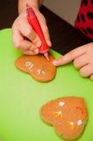 Muchacha que adorna el pan de jengibre Fotos de archivo libres de regalías