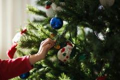 Muchacha que adorna un árbol de navidad Fotos de archivo