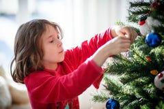 Muchacha que adorna un árbol de navidad Imagenes de archivo