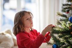 Muchacha que adorna un árbol de navidad Imágenes de archivo libres de regalías