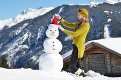 Muchacha que adorna un muñeco de nieve Fotografía de archivo libre de regalías