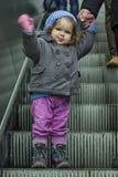 Muchacha que agita en la escalera móvil Imagen de archivo
