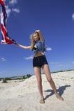 Muchacha que agita la bandera de Gran Bretaña y que fija su pelo Fotos de archivo libres de regalías