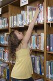 Muchacha que alcanza para un libro en biblioteca Imagen de archivo libre de regalías