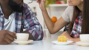 Muchacha que alimenta al novio afroamericano con la torta sabrosa, café de consumición de los pares almacen de video