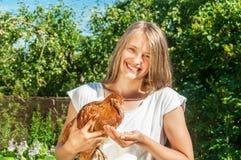 Muchacha que alimenta el pollo marrón Foto de archivo libre de regalías