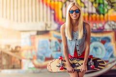 Muchacha que anda en monopatín hermosa Foto de archivo libre de regalías