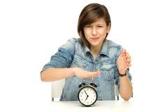 Muchacha que apaga el reloj de alarma Imagen de archivo