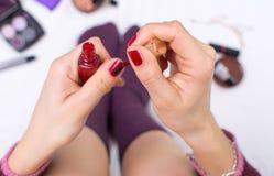Muchacha que aplica esmalte de uñas en cama Fotografía de archivo