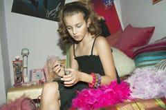 Muchacha que aplica esmalte de uñas en dormitorio Fotografía de archivo libre de regalías