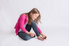 Muchacha que aplica esmalte de uñas a los dedos del pie Foto de archivo