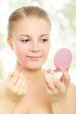 Muchacha que aplica lápiz-maquillaje del labio Imagen de archivo libre de regalías