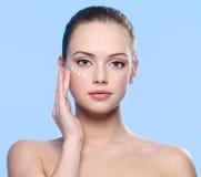 Muchacha que aplica la crema cosmética alrededor de ojos Imagenes de archivo