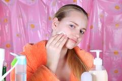 Muchacha que aplica la loción en la cara, cuidado de piel diario Foto de archivo