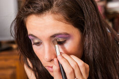 Muchacha que aplica maquillaje Fotos de archivo libres de regalías