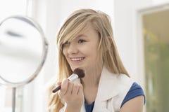 Muchacha que aplica maquillaje delante del espejo en casa Fotografía de archivo
