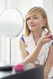 Muchacha que aplica maquillaje delante del espejo en casa Imagen de archivo libre de regalías