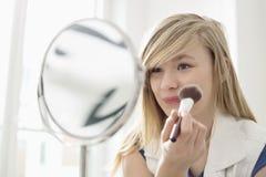Muchacha que aplica maquillaje delante del espejo en casa Imágenes de archivo libres de regalías