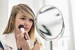 Muchacha que aplica maquillaje delante del espejo en casa Foto de archivo libre de regalías