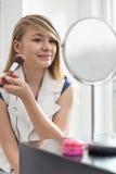 Muchacha que aplica maquillaje delante del espejo en casa Fotografía de archivo libre de regalías
